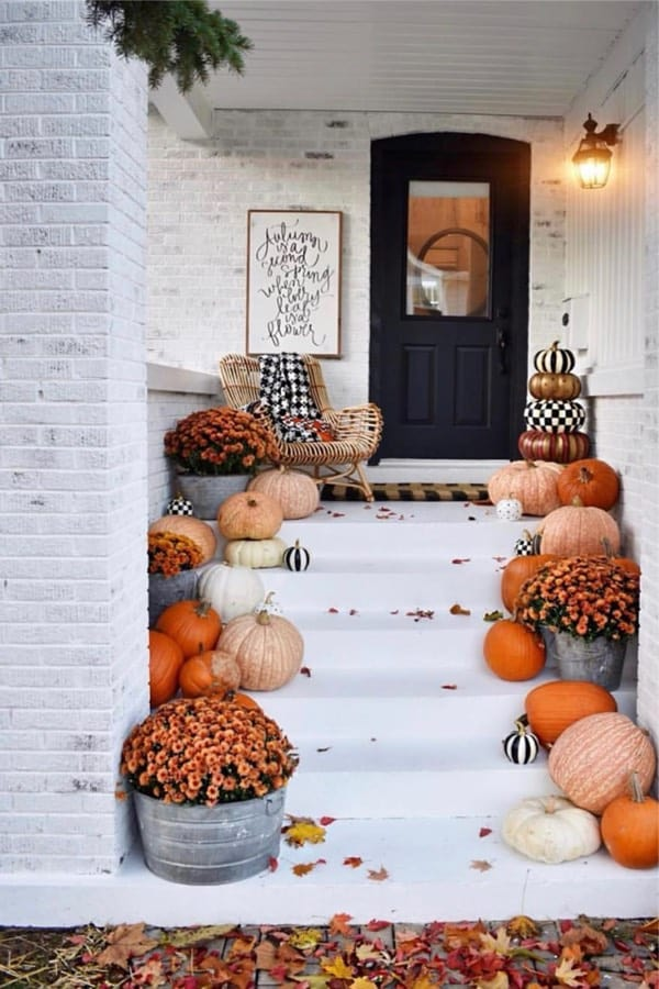 white front porch with pumpkins