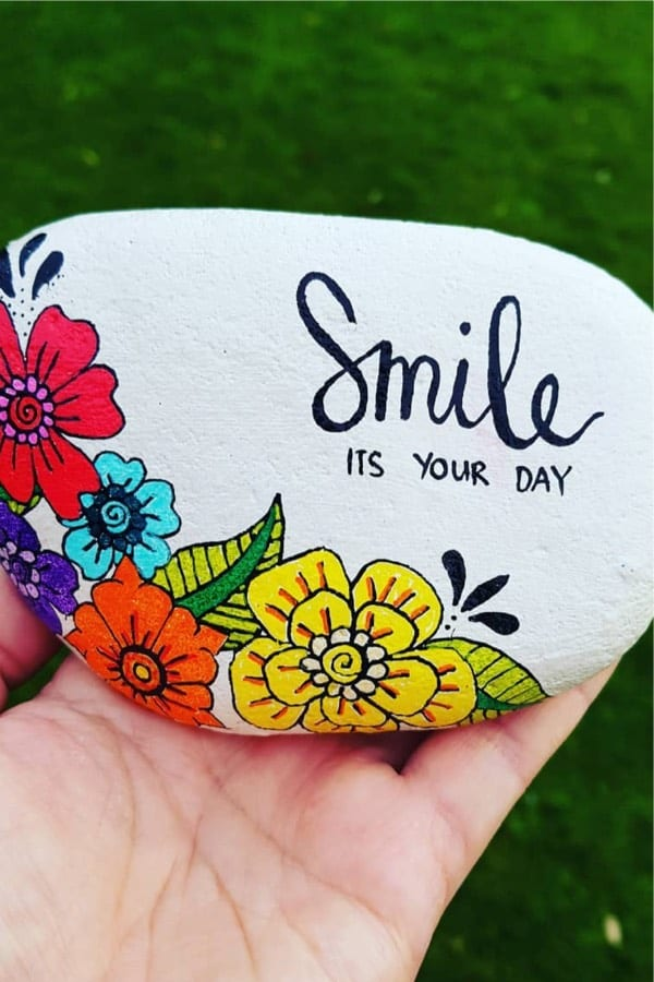 white painted rock with colorful flower designs